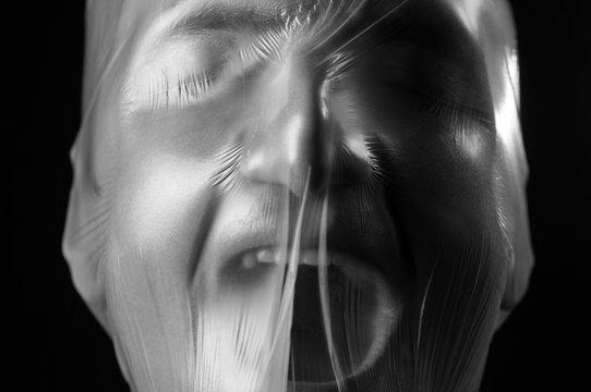 close-up portrait of a plastic bag on the face asphyxiation