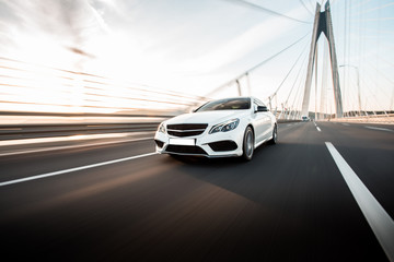 White business class sedan car driving on the highway over the bridge in the daytime Fototapete
