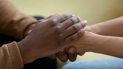 Fototapeta Close up african american man hands holding upset depressed woman, comforting wife for supporting frustrated disappointed girlfriend having life problem, showing love and support. obraz