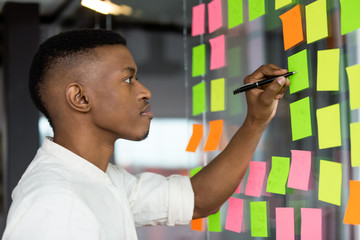 Focused African American male employee brainstorm write ideas on colorful sticky note pads on glass wall in office, thoughtful biracial man do creative thinking develop company startup in boardroom
