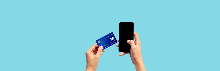 Woman hand holding blue credit card and using smart phone isolated on blue background, front side view. Blue bank-card design mock up. mobile payment ,online shopping concept