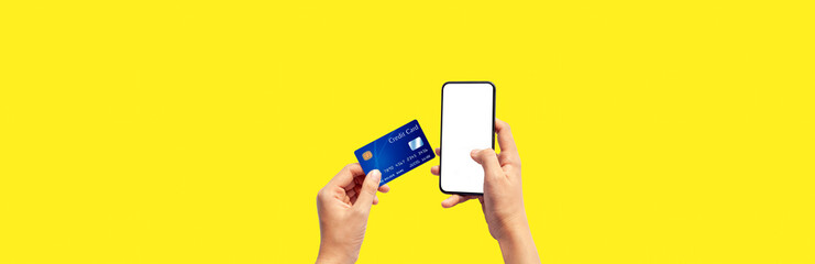 Woman hand holding blue credit card and using smart phone isolated on yellow background, front side view. Blue bank-card design mock up. mobile payment ,online shopping concept