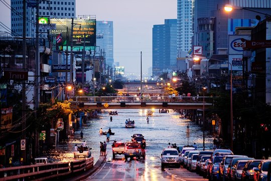People And Vehicles On Road During Floods In City At Dusk