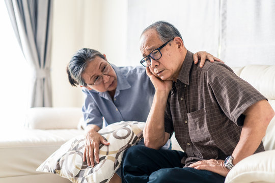 Asian senior old man having headache stress problem put hand on temple sitting on sofa at home. Elder wife sit beside consoling husband put hug, put hand on shoulder. Make comfort talking to relax him