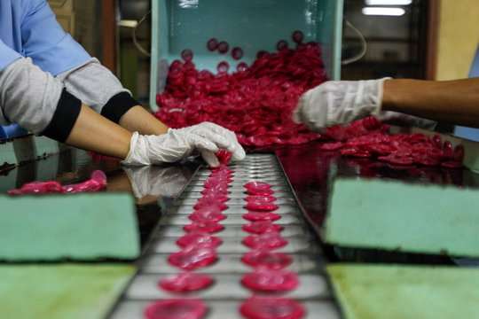 Cropped Hands Of Workers Arranging Condoms In Production Line At Factory