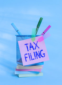 Text sign showing Tax Filing. Business photo text Submitting documens filed with tax payer financial information Sticky note arrow banners stacked pads metal pens holder pastel background