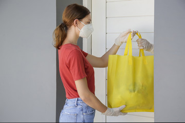 Volunteer women brings a bag with food and another unessesary groceries for persons in need. Delivery to the door. Food delivery services during coronavirus pandemic.