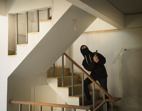Thief Holding Gun While Standing On Staircase In Building