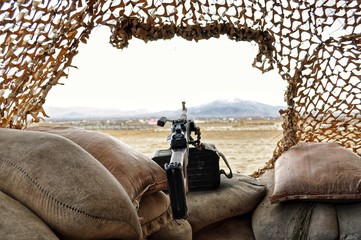 Close-up Of Gun On Sacks Against Clear Sky