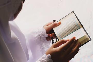 Close-up Of Woman Reading Koran