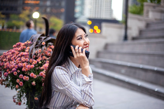 happy Asian business woman with long black hair wearing a trendy corporate shirt and skirt is sitting confidently at an outdoor park talking on a cell phone enjoying the view of Chicago downtown