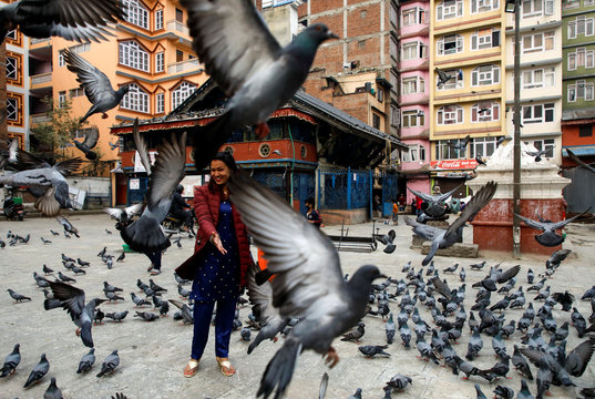 A woman reacts as pigeons take flight during the Nepalese New Year as the lockdown continues for the twenty-first day amid concerns about the spread of the coronavirus disease (COVID-19), in Kathmandu, Nepal