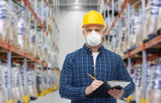 health care, work and pandemic concept - male worker in safety helmet wearing face protective mask or respirator with clipboard and pencil over warehouse background