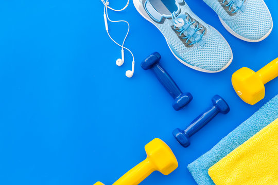Fitness set with sneakers, dumbbells, towel on blue background top view copy space