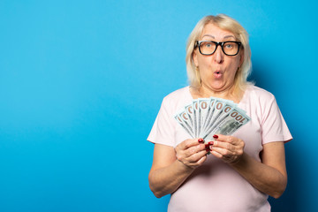 Portrait of an old friendly woman with a surprised face in a casual t-shirt and glasses holding money in her hands on an isolated blue background. Emotional face. Concept wealth, win, loan, pension