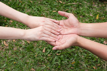 Hand hold together,shake hand and show concern,take care and give hope.nature green grass background.