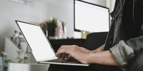 Cropped image of smart man's hands typing on white blank screen computer laptop that putting on his lap over comfortable sitting room as background. Work from home and remote working concept. Fotomurales