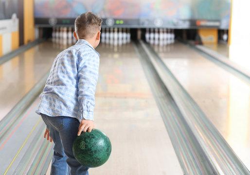 Little boy playing bowling in club