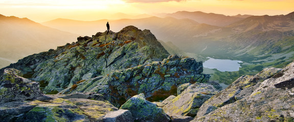 Photo sur Plexiglas Cappuccino Banner, web page or cover template of Man on the top of the hill watching wonderful scenery in mountains during summer colorful sunset in High Tatras in Slovakia. Copy space and panoramic ratio