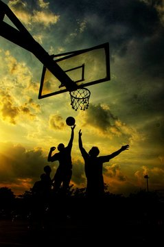 Silhouette Of Men Playing Basketball Against Sky During Sunset