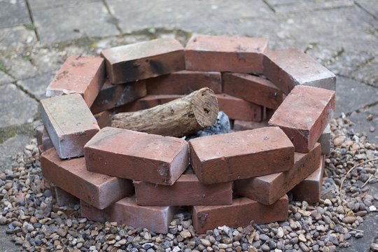 Home made brick built fire pit or barbecue with logs