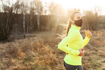 Woman in medical mask is jogging outdoors