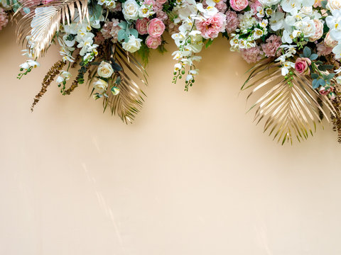 Celebration decoration background with gold tropical palm leaves with white and pink roses flower bouquet.