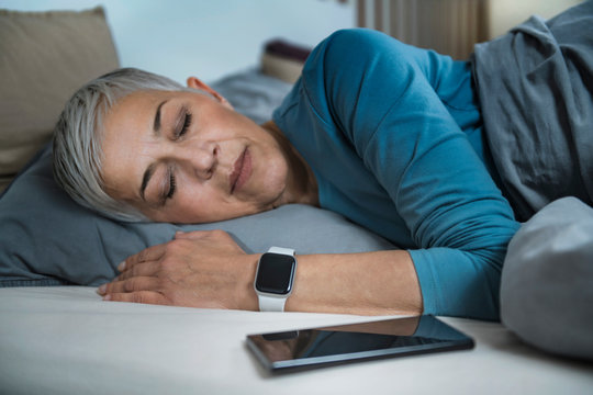 Sleep Apps - Tech-savvy Senior Woman Sleeping in Bed, Using Smart Phone and Smart Watch to Improve her Sleeping Habits