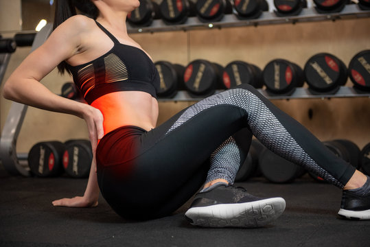Woman feeling back pain while exercising in gym