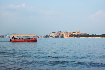 Wall Mural - Toruist boat in Lake Pichola with City Palace in background. Udaipur, Rajasthan, India