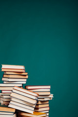 many stacks of educational books to teach in the school library on a green background