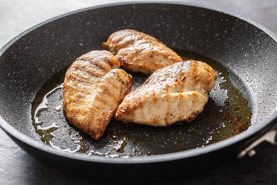 Pan-fried juicy chicken breasts on a dark pan