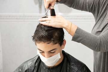 Son with facial mask while his mother cuts his hair at home