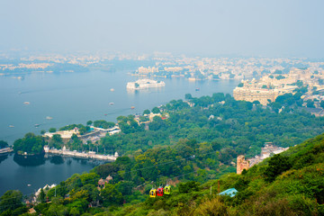 Wall Mural - Aerial view of Lake Pichola with Lake Palace (Jag Niwas) and City Palace and cable car rope way. Udaipur, Rajasthan, India