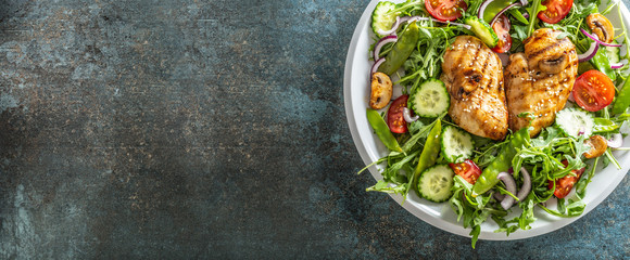 Top view of a healthy chicken salad in a white plate placed on the right half of the black rustic surface Fototapete