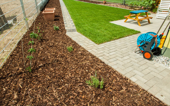 Garden with fresh new lawn and bark mulch area to reduce weed growth