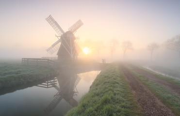 Wall Mural - windmill in dense fog at sunrise