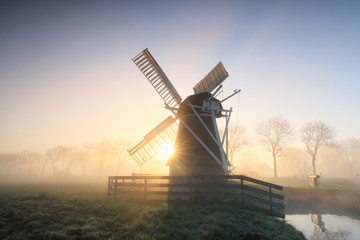 Wall Mural - charming Dutch windmill in fog at dawn