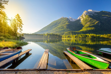 Sunny morning near the lake with boats and mountains Wall mural