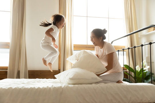 In morning carefree small daughter jump on bed while vietnamese mother laughing feels happy, asian ethnicity family in comfortable pyjamas wake up start new day positive mood enjoy active life concept
