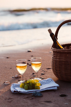 Wine In Glasses By Basket At Beach Against Sky During Sunset