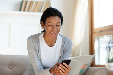 Millennial black girl hold smartphone in hands, smiling and looking at screen. Chatting in messenger or social networks, type email or message on phone, video call, online shopping, surfing internet