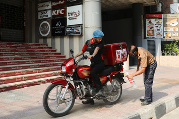 A man sprays sanitizer on a food delivery motorbike amid concerns over the coronavirus disease (COVID-19) outbreak in Dhaka