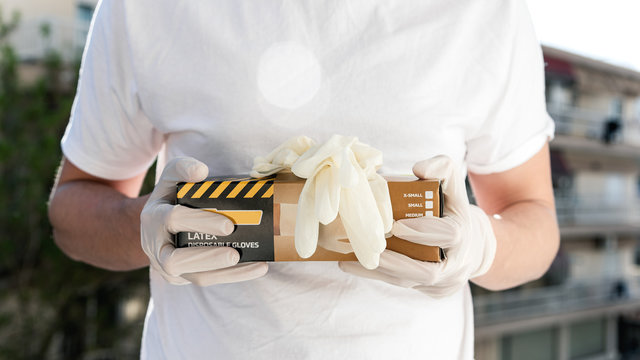 Person with surgical gloves holding a box of disposable latex gloves. Covid-19 pandemic.