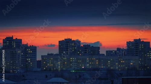 Fotobehang Sunset skyline city buildings silhouettes windows light up dusk to night change. Timelapse, 4K UHD.