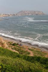 Klif na peruwiańskim wybrzeżu Pacyfiku z widoczną plażą i molem.