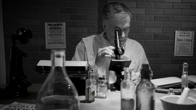 In black and white a scientist during the 1918 influenza pandemic working in his private laboratory searching for a cure to the Spanish Flu.