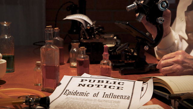 Notice of the influenza epidemic of the year 1918 lying on the laboratory table of a medical research scientist studying the virus.