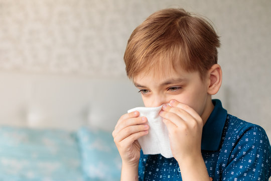 Young boy  with allergy sneezing and blowing his nose in a handkerchief. House background
