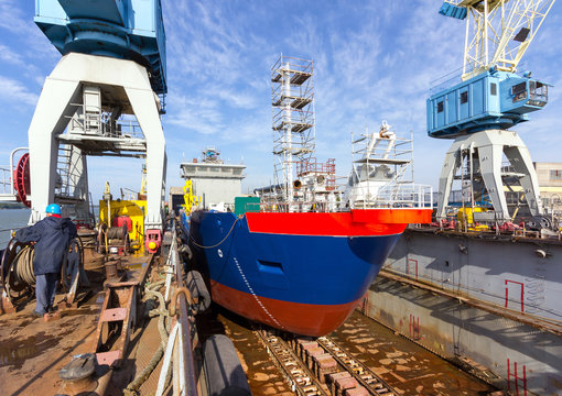 A cargo ship is building in a dock at a shipyard